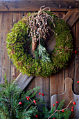 Moss wreath with pine, spruce cones and branch with palm berries
