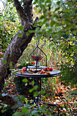 Posy of rose hips and privet berries on table in garden decorated with apples and autumn leaves