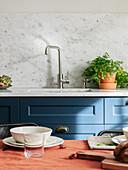 Blick vom gedeckten Esstisch auf die blaue Küchenzeile mit Spüle