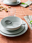 Table set with orange tablecloth and white crockery