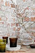 Zweig in klarer Kugelvase und farbige Glasvasen vor Backsteinwand