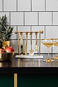 Goldenes Cocktail-Besteck an einer Hänge-Aufbewahrung in der Küche