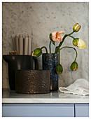 Aufblühende Mohnknospen in rustikaler Vase und Kanne mit Kerzen