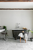Small, free-standing bathtub in simple bathroom in grey and white