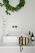 Wreath of leaves above square countertop sink
