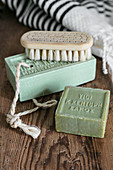 Bars of green soap and brush on wooden board