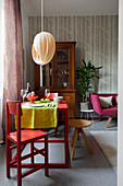 Red dining table set for dinner in front of dresser in living room