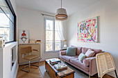 Pink sofa in small, eclectic living room