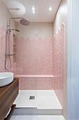 Rosafarbene Fliesen im Fischgrätmuster im kleinen Bad mit Dusche