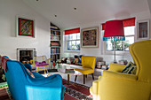 Upholstered seating in yellow and blue in small living room with colourful accessories