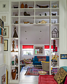 Collection of sculptures on shelves surrounding open doorway leading into living room