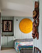 Ethnic sculpture in bedroom with pale blue wood panelling