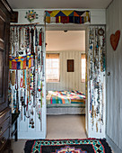 Collection of necklaces hanging on walls flanking doorway leading into bedroom