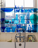 Blue glass vases and bottles on shelves in window