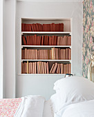 Books with covers in shades of red and pink on shelves in bedroom