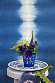 Anemone, goldenrod, veronica and sea holly in front of blue ikat pattern