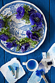 Wreath of anemones on blue plate, artists' pastels and painting utensils