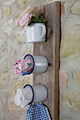 Organiser made from enamel mugs on wooden board leaning against rustic stone wall