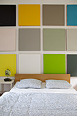 Wall decorated with multicoloured squares above bed in bedroom