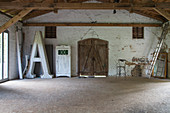 Huge illuminated letter A in old barn with chipboard panels on floor