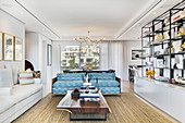 Shelves, coffee table and turquoise sofa in bright living room