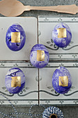 Purple marbled Easter eggs decorated with gold leaf