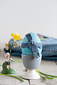 Blue Easter egg decorated with denim ribbon in egg cup