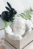 Blown goose egg decorated with pattern of drilled holes