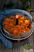 Lit candle and marigolds wrapped in felt in tart case
