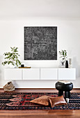 White floating sideboard, modern artwork and houseplants in living room