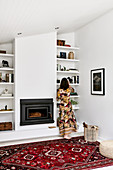 Woman standing in front of shelves next to fireplace in living room
