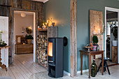 Log burner and stacked firewood in hallway