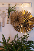 Handmade paper stars and spruce twigs hanging from coat rack