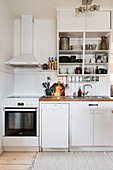 Cooker below extractor hood in charming white kitchen