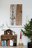 Christmas pictures drawn on wooden boards above nativity set on wooden crate