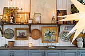Alte Bilder, Trödel und Kerzen auf einem Regal an der Bretterwand