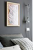 Abstract picture on wall and light bulb on cable above bed as bedside light