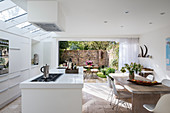 Open-plan kitchen with access to garden in white, modern interior