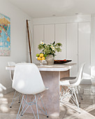 Shell chairs at table in front of fitted cupboards in white dining room