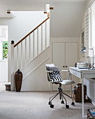 Desk in front of staircase with fitted under-stair cupboards in foyer