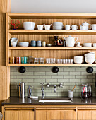 Crockery and glasses on shelves above sink in modern kitchen