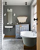 Free-standing bathtub on wooden block in vintage-style bathroom