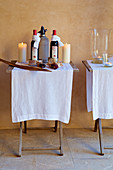 White cloths, wine bottles and candles on two folding tables