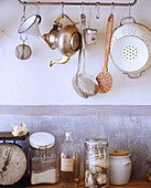 Kitchen utensils hung from rod against wall with patina