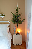 Fir tree and Madonna figurine on bedside table in bedroom