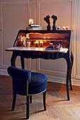 Brennende Teelichter auf Sekretär im Rokokostil davor dunkelblauer Polsterstuhl