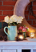 Pine cones, tealights in glass holders and jug of white roses decorating sideboard