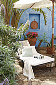 Lounger below parasol in front of pale blue wall in summery garden