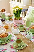 Romantischer Ostertisch mit grünem Geschirr und geblümten Tischsets