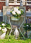 Madonna figurine on lawn below hydrangeas on old washstand